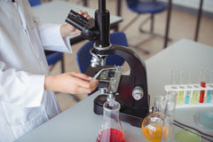 Mediados de sección de la colegiala que experimenta en el microscopio en laboratorio Foto de archivo