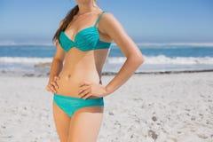 Mediados de sección de la mujer del ajuste en bikini en la playa Fotos de archivo