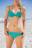 Mediados de sección de la mujer del ajuste en bikini en la playa Fotografía de archivo