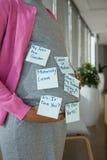Mediados de sección de la mujer embarazada que se coloca con las notas pegajosas sobre su estómago imagenes de archivo