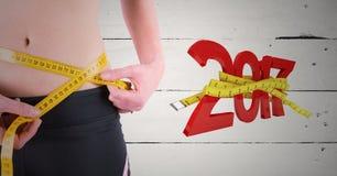 Mediados de-sección de la mujer que mide su cintura contra el Año Nuevo 3D 2017 Fotografía de archivo