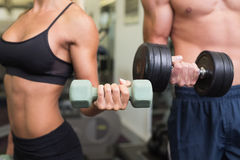 Mediados de sección de los pares que ejercitan con pesas de gimnasia en gimnasio Imagenes de archivo