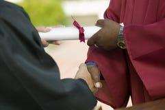 Mediados de sección de recepción graduada del diploma y del apretón de manos Foto de archivo libre de regalías