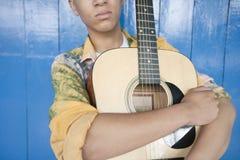 Mediados de sección de un adolescente con la guitarra contra el revestimiento de madera de madera Foto de archivo