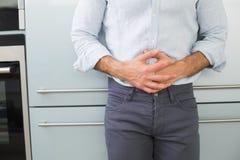 Mediados de sección de un hombre que sufre de dolor de estómago Imagenes de archivo