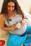 Mediados de sección de un reloj que se sostiene femenino embarazada Fotos de archivo libres de regalías