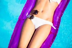 Mediados de sección de una mujer en el bikini blanco que miente en cama de aire en piscina Imagen de archivo libre de regalías