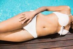 Mediados de sección de una mujer en el bikini blanco que miente por el lado de la piscina Imágenes de archivo libres de regalías