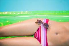 Mediados de sección de una mujer en el bikini que miente en cama de aire con las gafas de sol Imagen de archivo libre de regalías