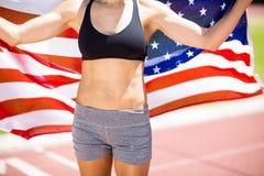Mediados de sección del atleta de sexo femenino que soporta la bandera americana en pista corriente Fotografía de archivo libre de regalías