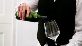 Mediados de sección del camarero que vierte el vino rojo en una copa de vino en el contador almacen de metraje de vídeo