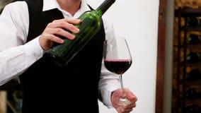 Mediados de sección del camarero que vierte el vino rojo en una copa de vino en el contador metrajes