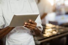 Mediados de sección del cocinero que usa la tableta digital Imagenes de archivo