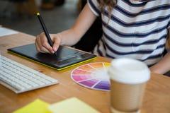 Mediados de sección del diseñador gráfico de sexo femenino que usa la tableta de gráficos en el escritorio Imagenes de archivo