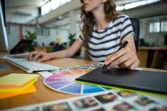 Mediados de sección del diseñador gráfico de sexo femenino que usa la tableta de gráficos en el escritorio Fotografía de archivo libre de regalías