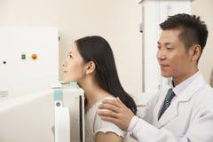Mediados de sección del doctor Examining Female Patient masculino con la máquina de radiografía imagen de archivo libre de regalías