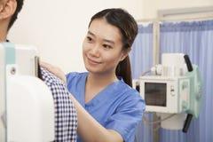 Mediados de sección del doctor Examining Male Patient femenino con la máquina de radiografía Fotos de archivo libres de regalías