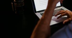 Mediados de sección del ejecutivo de sexo masculino caucásico joven que trabaja en el ordenador portátil en la tabla en la oficin almacen de metraje de vídeo