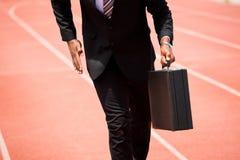 Mediados de sección del hombre de negocios que corre en una pista corriente Fotografía de archivo