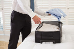 Mediados de sección del hombre de negocios que desempaqueta el equipaje en el hotel Fotografía de archivo libre de regalías
