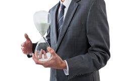 Mediados de sección del hombre de negocios que sostiene el reloj de arena Foto de archivo libre de regalías