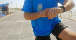 Mediados de sección del hombre mayor activo que comprueba tiempo en smartwatch en una 'promenade' en la playa 4k almacen de metraje de vídeo