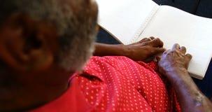 Mediados de sección del hombre mayor ciego que lee un libro de braille en la clínica de reposo 4k almacen de video