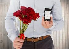 Mediados de-sección del hombre que sostiene el ramo del anillo de compromiso y de la flor Imágenes de archivo libres de regalías