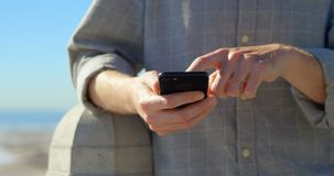 Mediados de sección del hombre usando el teléfono móvil en la 'promenade' 4k metrajes