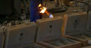 Mediados de sección del molde de metal de calefacción del trabajador con la lámpara de soldar en el taller 4k de la fundición metrajes