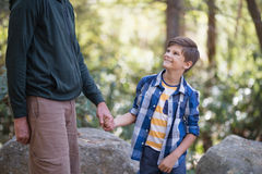 Mediados de sección del padre que lleva a cabo la mano del muchacho en bosque Imagen de archivo