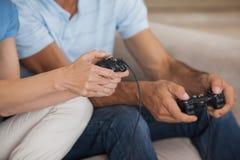 Mediados de sección del primer de los pares que juegan a los videojuegos Fotografía de archivo