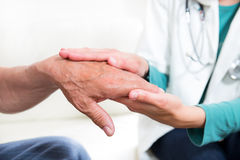 Mediados de sección del primer de un doctor que lleva a cabo las manos de los pacientes Imagen de archivo