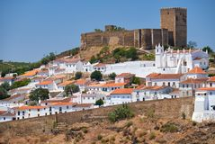 The mediaeval castle on the top of the hill surrounded by reside. Ntial Alentejo country-style houses inside the old city walls of Mertola Royalty Free Stock Photos