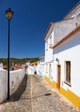 The mediaeval castle on the top of the hill surrounded by reside. Ntial Alentejo country-style houses inside the old city walls of Mertola Stock Photography
