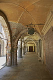Mediaeval vaulting, Avigliana, Italy. A vaulted arcade dating back to medieaval times shelters shops in Avigliana, Piedmont Italy. The plaster is missing in Stock Photos