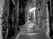 Mediaeval village alley, alleyway with light at end of tunnel. Monochrome. Taken in a medieval village in Lunigiana, north Tuscany. Largely deserted now due to Royalty Free Stock Photography