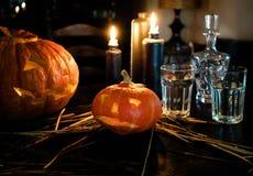 medianoche Víspera de Todos los Santos calabazas y velas, vidrios del jarro con agua Fotografía de archivo