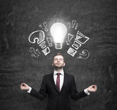 Mediating manager ponders about new business ideas. A light bulb as a concept of new ideas Royalty Free Stock Photos