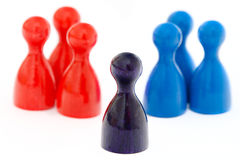 Mediation. Purple game figurine standing between a group of red and blue figurines, symbolizing conflict solution and mediation Royalty Free Stock Photos