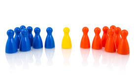 Mediation concept. Yellow pawn in the middle between red and blue pawns Stock Photo
