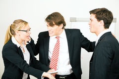 The mediator. Business: Team having a serious argument, one colleague being the mediator Stock Photo