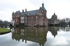 Mediaval Castle with castlemoat and drawbridge. Mediaval Castle and reflections of the castle in castlemoat in the German village Anholt, Castle has two royalty free stock photos
