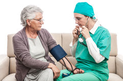 Medic blood pressure check old woman at home Royalty Free Stock Image