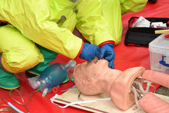Medic in breathing apparatus and protective suit practices resuscitation. Stock Photography