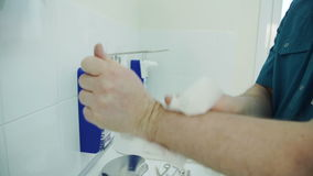 The medic carefully wipes his hands with a napkin over the sink. stock video footage