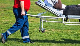 Medic Carries The Injured Football Player Royalty Free Stock Photo