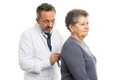 Medic checking patient by listening with stethoscope royalty free stock image