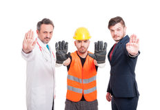 Medic with constructor and businessman showing stop sign Stock Photo