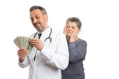 Medic counting money with patient looking stock photography